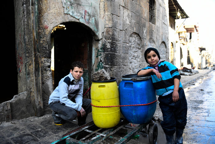 Two Syrian boys rest beside a cart they use to carry water back to their home in east Aleppo.