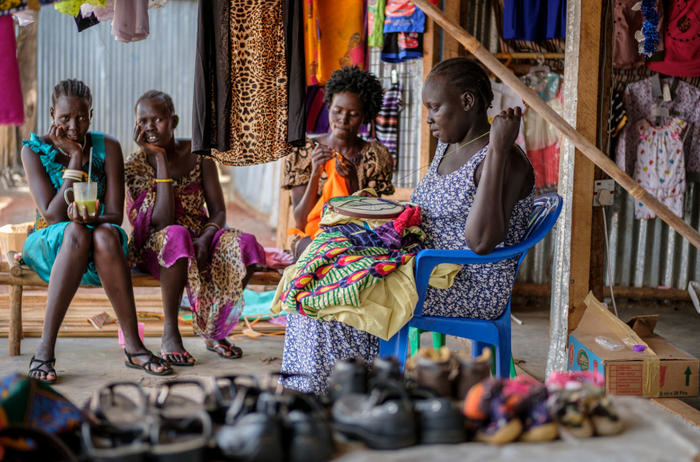 A South Sudanese woman mends a shirt for a customer at a market in Nymanzi refugee settlement in Northern Uganda.