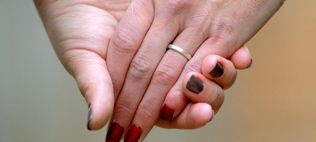 Women hold hands in Canberra