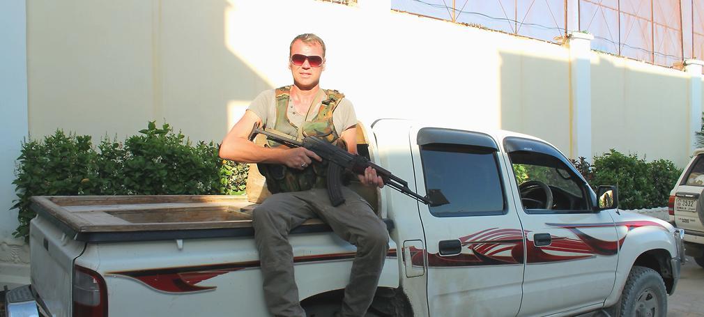 man sitting on a pickup truck in mogadishu holding a machine gun