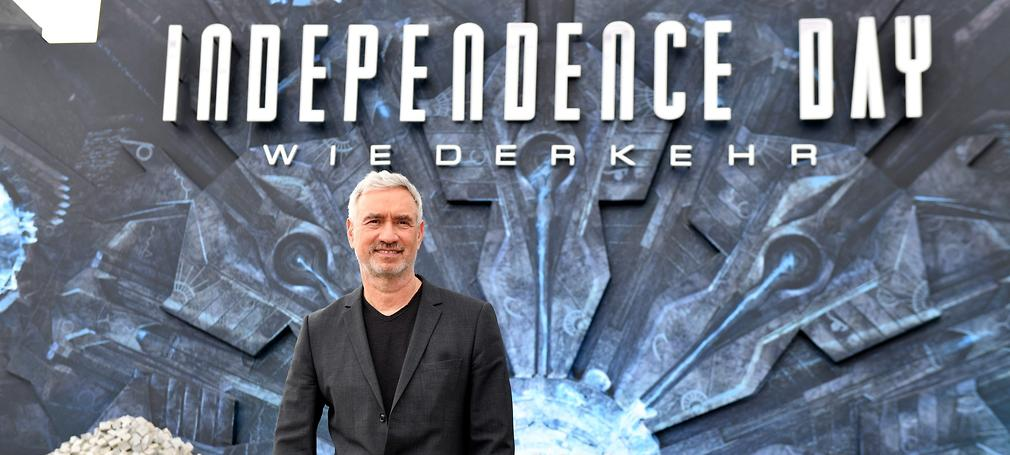 Roland Emmerich poses in front of an independence day sign.