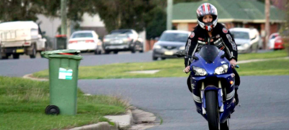 Conroy riding a motorcycle down a street in Wagga.