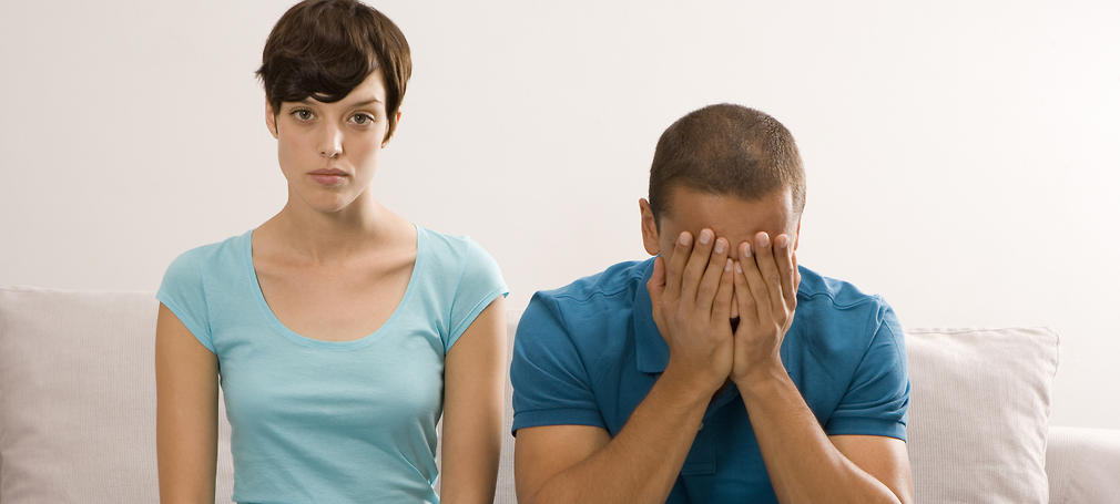 Man and woman sit on a couch, upset