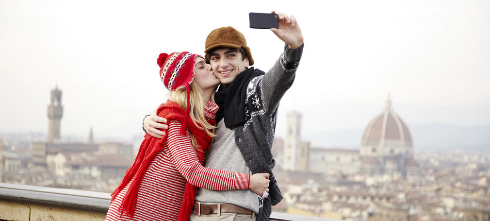 A couple take a photo of themselves kissing