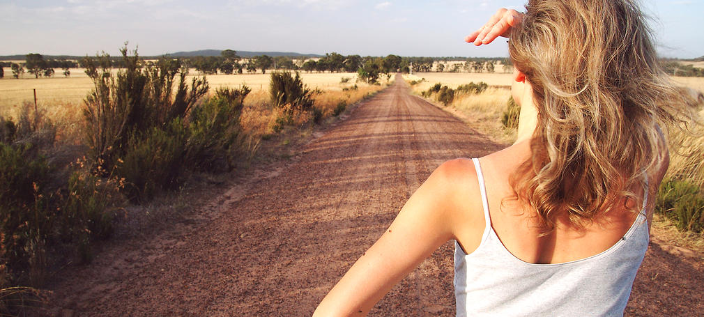 A woman looks down a long dirt track.