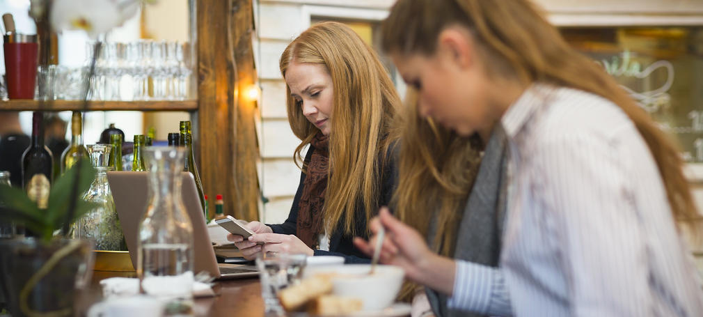 A woman sits at a restaurant on her phone.