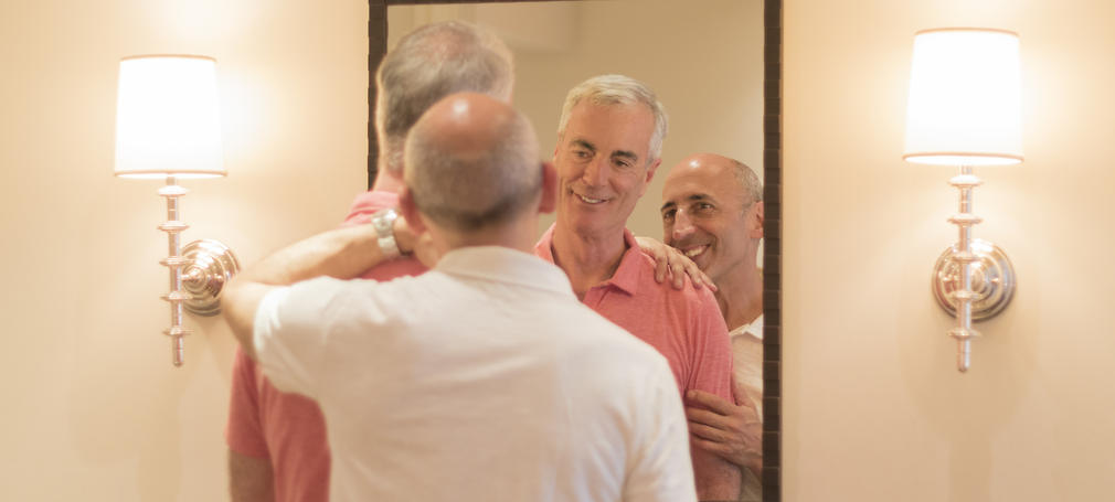 Senior Gay Couple Affectionately Looking at Each Other in Mirror