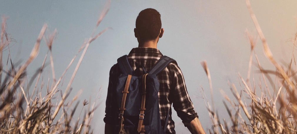 A young person with a backpack looks forward in a field of scrub.