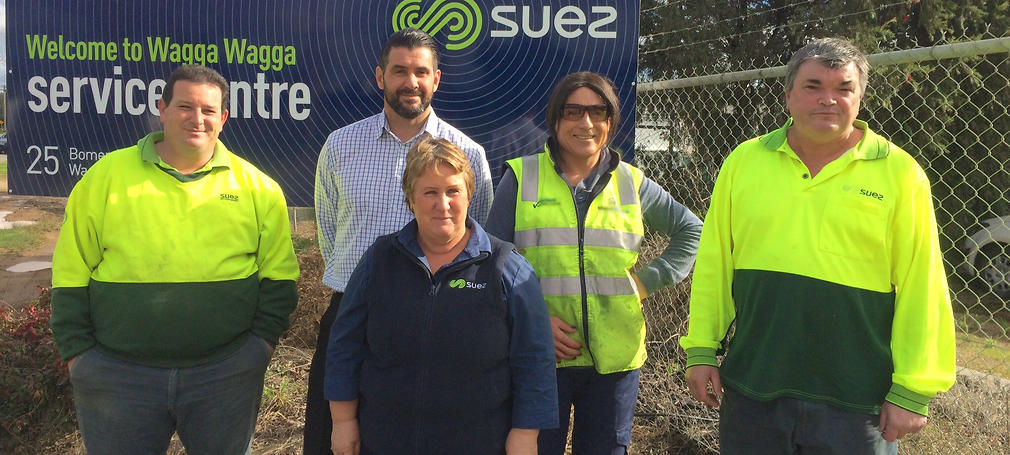 Holly Conroy stands with workmates in a high vis vest.