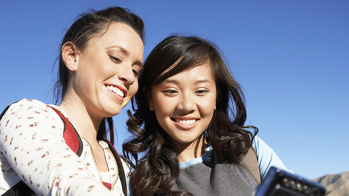 Two young women standing with bicycle taking a selfie