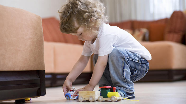Blonde toddler playing with toy train on floor