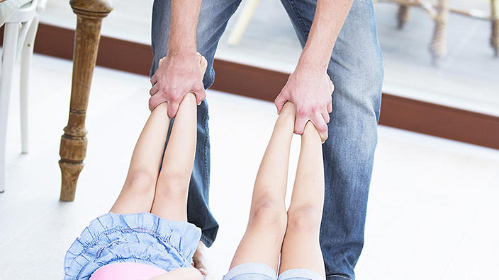 Low section of playful father dragging girls on hardwood floor