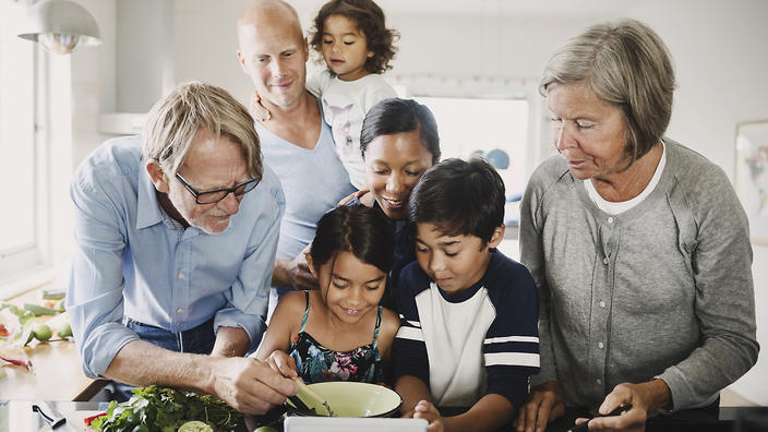 A family preparing food at kitchen counter