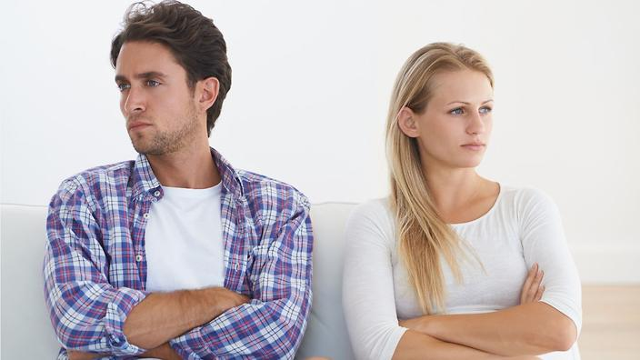 two people sit on a couch with crossed arms