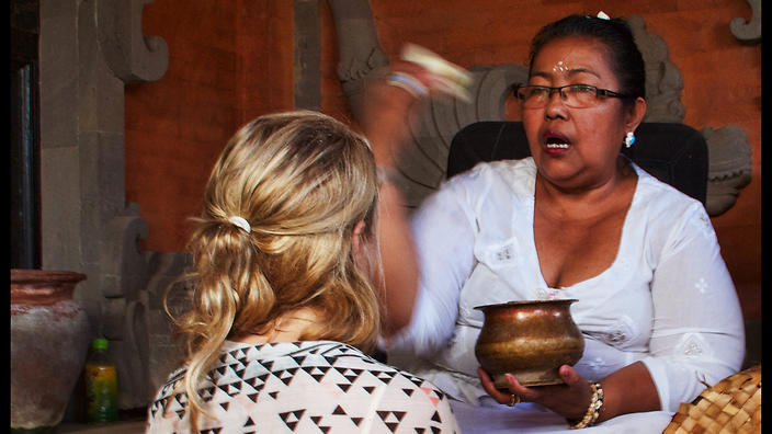 A woman is blessed with holy water as part of her treatment with a balian.