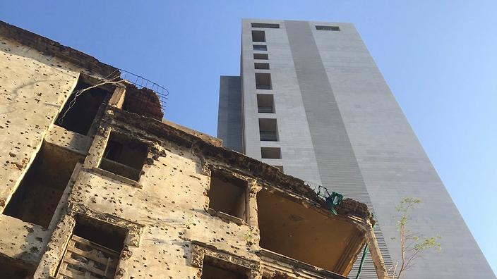 A building damaged in the civil war is overshadowed by a new residential high rise in Beirut's Sodeco neighbourhood.