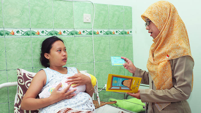 A mother and her newborn with a midwife, after cord blood has been collected.