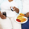 Overweight Couple sitting eating junk food holding remote control