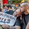 A man holds another man who holds a homophobia kills sign.