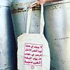 A white tote bag with pink Arabic script.