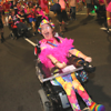 A woman in bright colours pilots a wheelchair down the Mardi Gras parade route.