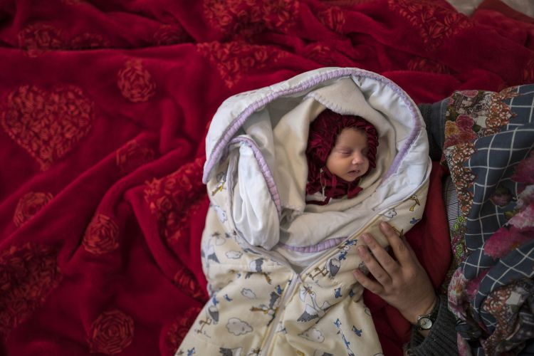 25-day-old premature Afghan infant Aliah lies on a bed next to her mother Shameem in a camp near the Croatian border in Serbia.