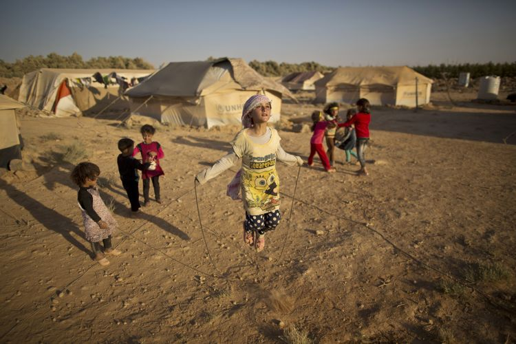 10-year-old Syrian refugee Zubaida Faisal, skips a rope while she and other children play near their tents at an informal tent settlement on the outskirts of Mafraq, Jordan.