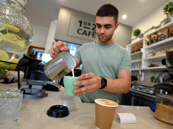 A barista is seen prepairing a coffee at a cafe in Canberra