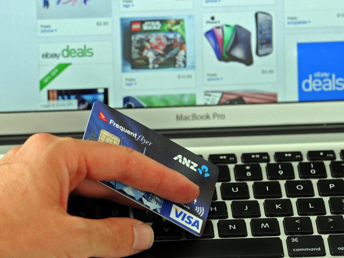 A credit card is held in front an online shopping site