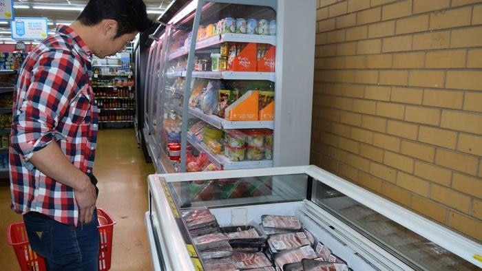 A Korean man shops in the new Asian food section