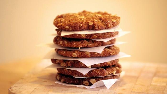 Freshly baked ANZAC biscuits are seen stacked on a wooden chopping board, Sydney, Wednesday, March 5, 2014. (AAP Image/Stephanie Flack) NO ARCHIVING