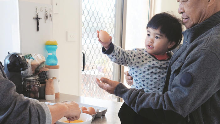 grandparents are whisking an egg and preparing breakfast with toddler