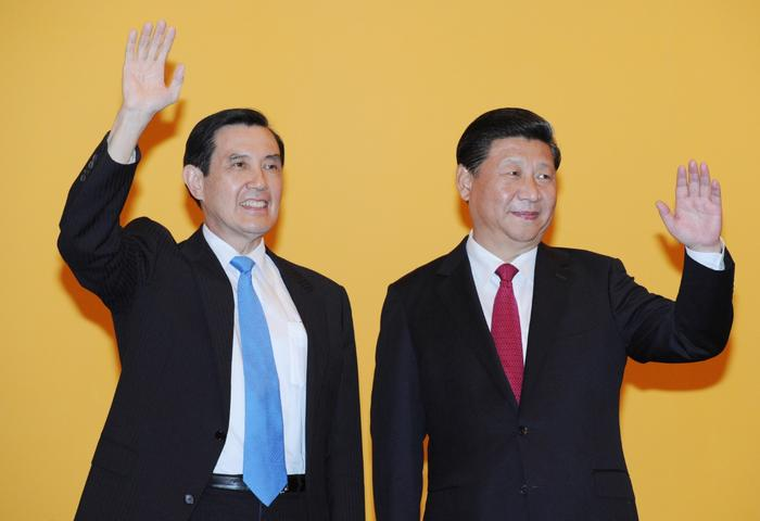 Chinese President Xi Jinping (R) and Taiwan President Ma Ying-jeou wave to the crowd of media before their historic meeting at Shangrila hotel in Singapore.